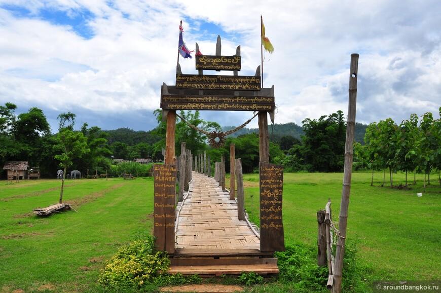 Мост заканчивается необычными воротами, исписанными на бирманском, тайском и английских языках, украшенными защитным амулетом, сплетённым из бамбука в виде солнца.