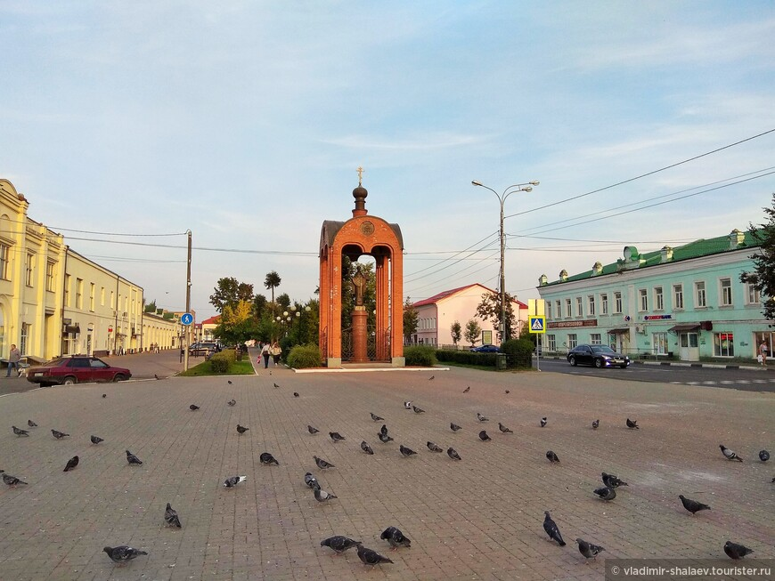 Можайск — город на западных рубежах Московской области. О том, что вы попали в самый центр города можно судить по этой Торговой площади. Торговцев в тот момент не было, зато было много голубей. На дальнем плане - кирпичная часовня-сень над металлической копией Николы Можайского. А за неё уходит Ленинский сквер. С обеих сторон от Московской улицы стоят несколько вековых каменных домов.