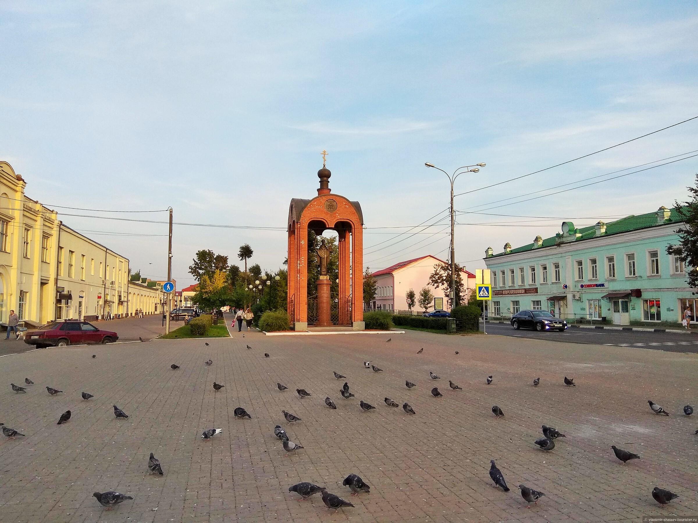Можайск — город на западных рубежах Московской области. О том, что вы попали в самый центр города можно судить по этой Торговой площади. Торговцев в тот момент не было, зато было много голубей. На дальнем плане - кирпичная часовня-сень над металлической копией Николы Можайского. А за неё уходит Ленинский сквер. С обеих сторон от Московской улицы стоят несколько вековых каменных домов., Попутный город