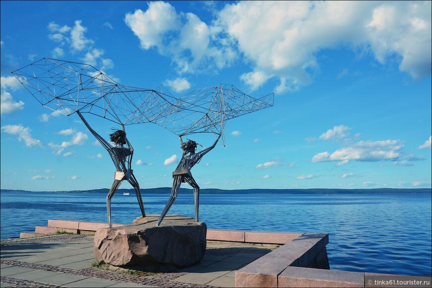 """Скульптура """"Рыбаки"""" на Онежской набережной превратилась в бренд Петрозаводска. Скульптура была подарена Петрозаводску американским городом Дулутом штата Миннесота, и в свое время открыла оригинальный музей под открытым небом. Скульптура составлена из металлических трубок, образующих тела двух рыбаков, которые закидывают сеть прямо в Онежское озеро."""