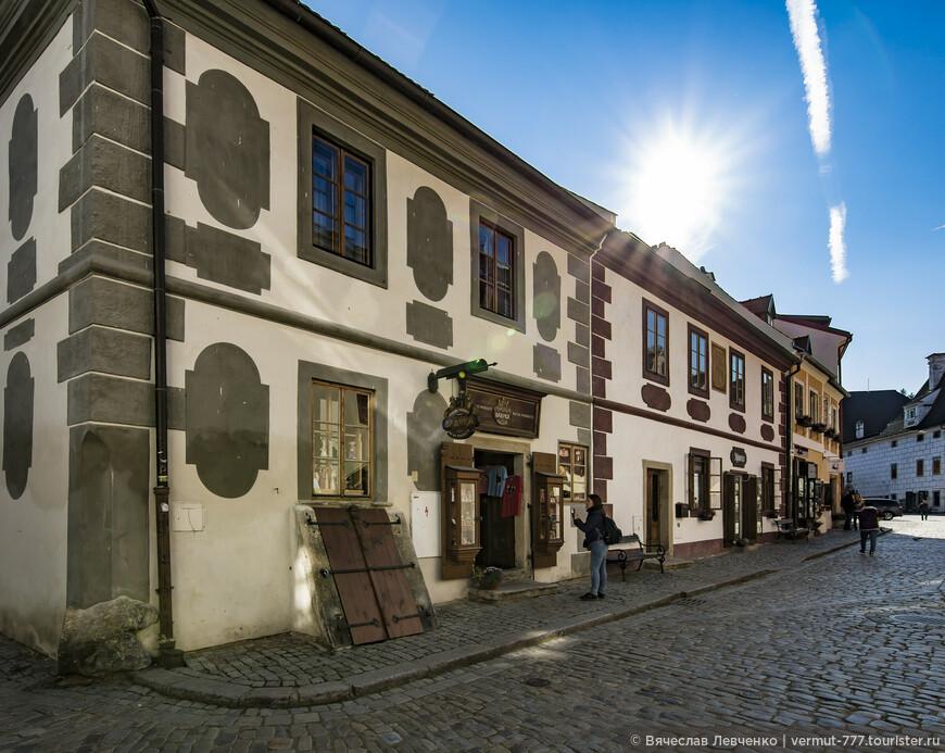 Слева, магазин BABYKA - přírodní produkty, по Široká 45. Первоначально здание готического ренессанса, облик которого во второй половине 17-го века был изменен в стиле раннего барокко - особенно фасад и фронтон, а также планировку дома. Нынешний облик дома является типичным примером архитектуры раннего барокко в городе Чески Крумлов.