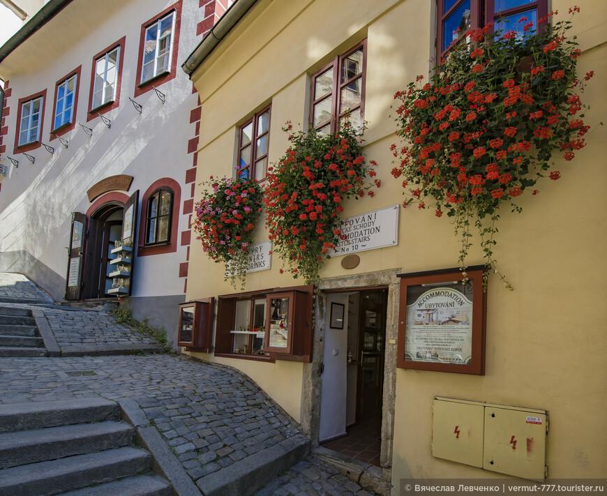 """Белое здание: Repliky - Historické Sklo S.r.o. - магазин стекла и зеркал, по улице Zámecké schody 11. Первые упоминания, когда этот дом  был подарен Петром IV Розенбергом в 1518 году  своему """"верному слуге"""" трубачу Каспару. В 1527 году вдова Каспара Манда (Магдалена) продала дом Михалу. Другим владельцем дома был канцлер Розенберга Микулаш Хульцшпорер из Гоштейна в начале 1640-х годов. В начале 19 века дом принадлежал трубочисту Антонину Гаушке.  В жёлтом доме находится пансион Ubytování Zámecké schody, по улице Zámecké schody 10. Здание начала 16-го века, не буду перечислять всех Иржиков и Анджейков, живших здесь, но все они были портные, парикмахеры и сапожники, очень уважаемые люди прошлых веков."""