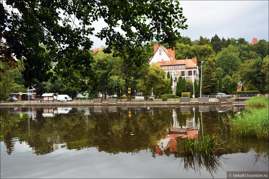 С одной стороны озера видны городские здания, в остальных случаях водоем опоясывает настоящий лесной бор.
