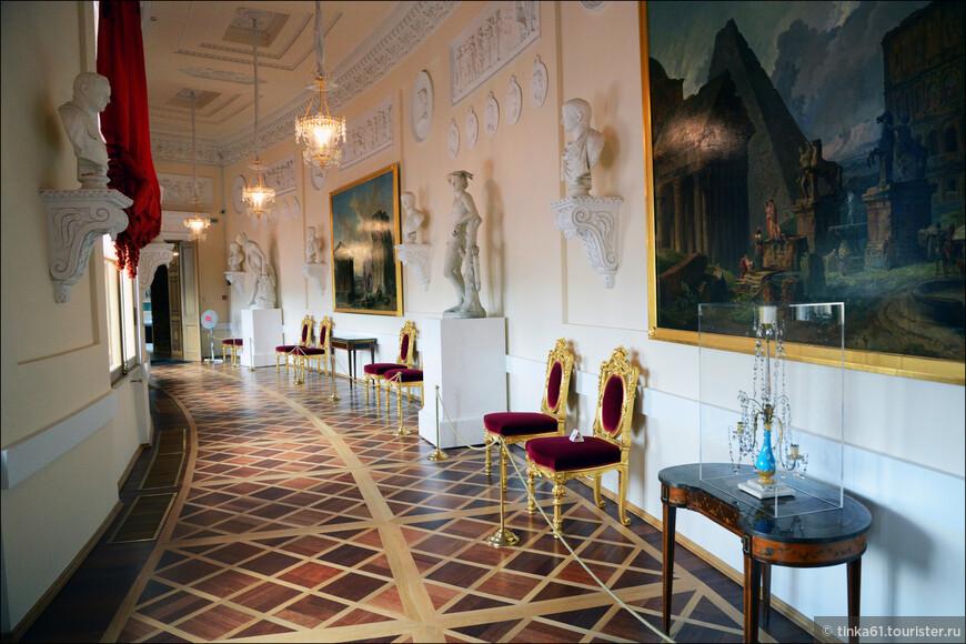 Греческая галерея связывает помещения бельэтажа главного корпуса дворца с Арсенальным каре и была задумана Павлом I как дворцовое собрание античности. Помещение представляло собой оригинальный дворцовый музей, посвященный искусству Древней Греции и Рима.