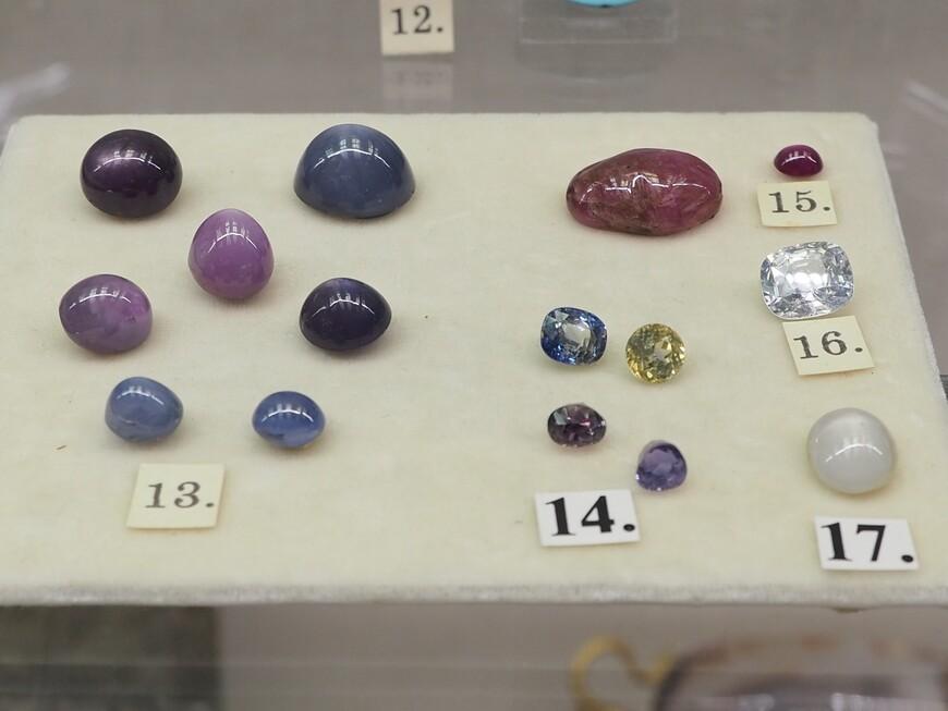 Это т.н. кабошоны - обработанные сапфиры и другие камни, все - дар Агафона Фаберже. Под номером 13 - сапфир звёздчатый из Шри-ланки. Под номером 14 - сапфиры разноцветные. 15 - рубин, 16 - лейкосапфир, 17 -  корунд звездчатый.