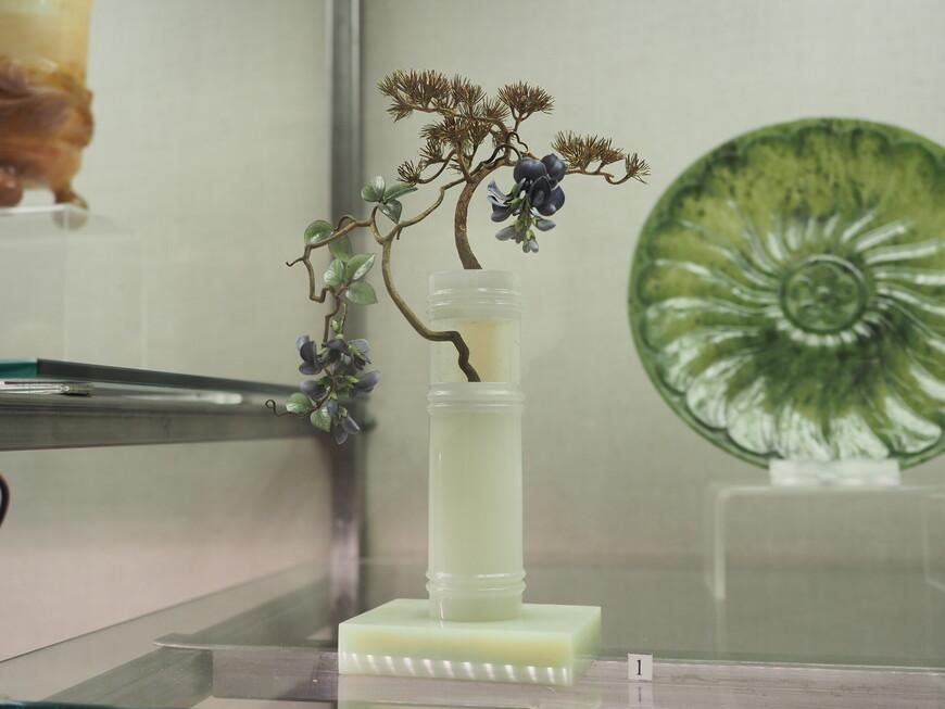 Пожалуй, самое изысканное изделие Фаберже в Минералогическом музее - маленькая композиция в стиле «бонсай»: крохотная золотая сосна, растущая из цилиндрического сосуда, обвитая цветущей лианой. Ствол лианы, как и сосны, золотой, листья нефритовые, а цветки - из зеленовато-серой и серовато-фиолетовой эмали. Среди пучков сосновых иголок - яркие изумрудные искры. Сосуд вырезан из мраморного оникса, а подставка под него - из благородного змеевика (бовенита). На изделии клеймо мастерской Ф.А.Афанасьева.