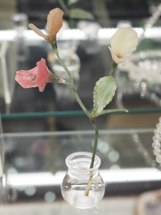 """Уникальный каменный цветок, изготовленный в московском отделении компании Фаберже, под названием """"Душистый горошек в вазочке"""". Лепестки цветов сделаны из белорецкого кварцита и родонита, вазочка """"с водой"""", как и во многих других цветочных композициях, из горного хрусталя. Применение горного хрусталя позволяет достичь уникального оптического эффекта, что цветы стоят в реальной воде, налитой в вазу. Как мастера Фаберже """"наливали"""" горный хрусталь в стеклянную вазочку - большой вопрос. А вот стебелек цветка сделан не из медных проволочек, обмотанных шелком, как это было обычно, а из нефрита. Франц Бирбаум считал, что это то же самое, что подковать блоху - сложно и не нужно. Каменный стебелек - большая редкость, в Москве такое изделие одно."""