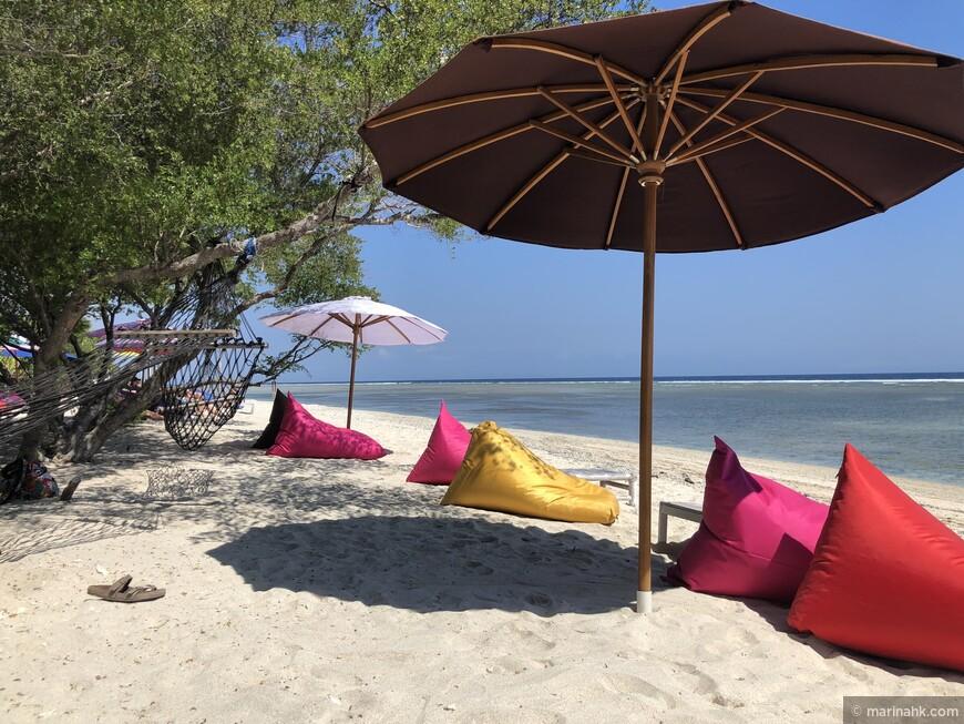 На многих пляжах есть такие разноцветные подушки и гамаки .