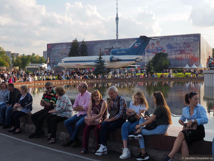 Вокруг бассейна, что под ракетоносителем, сидят сотни туристов