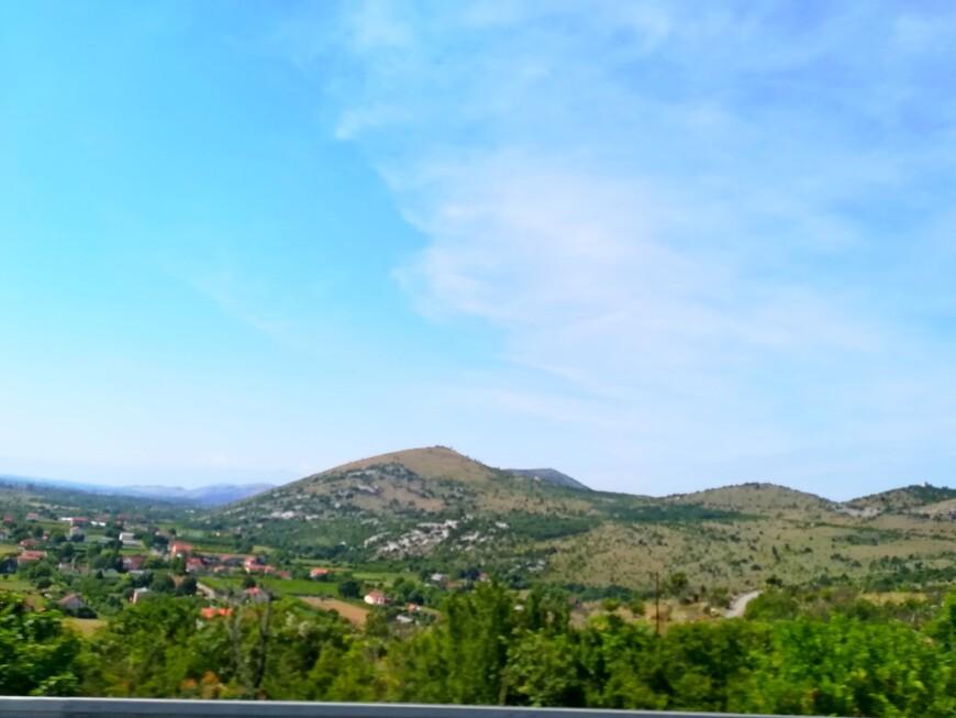 И вновь за стеклом черногорские красоты. Насмотреться невозможно. Очаровывает всё: аккуратные белые домики с красной черепичной крышей, роскошные пышные деревья, величественные горы, синее небо.