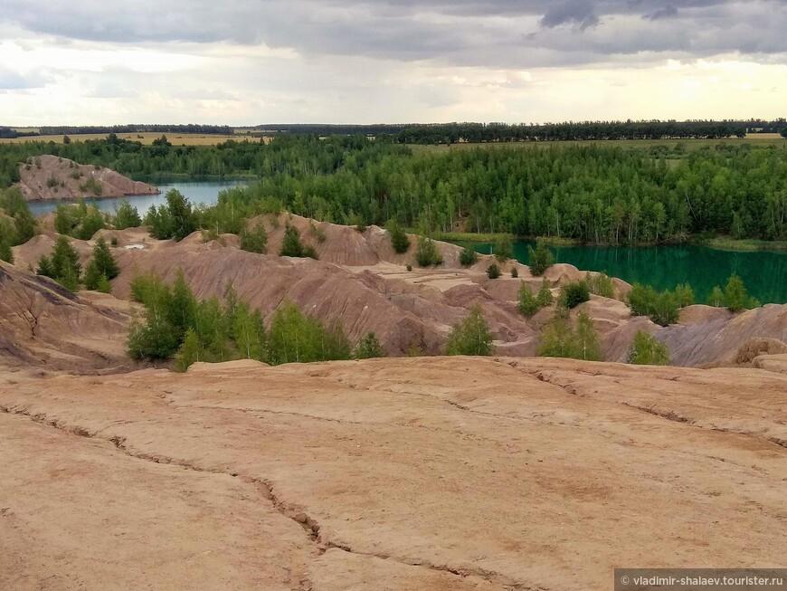 Отвалы отработанной породы возвышаются над озером как скалистые массивы.