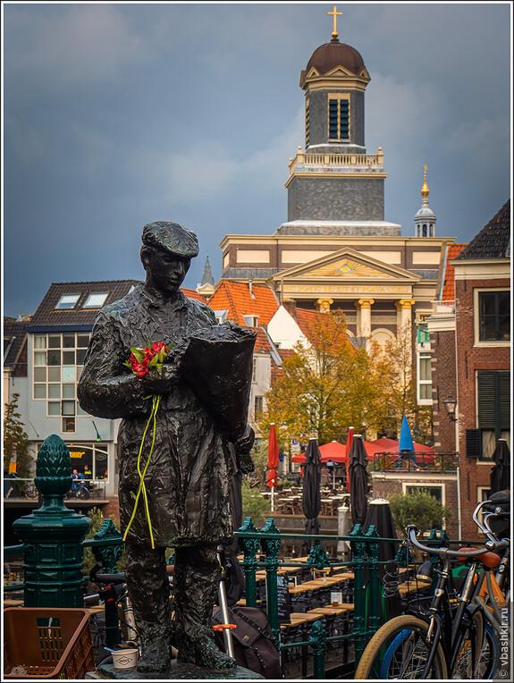 Лейден. Человек с цветами и церковь Hartebrugkerk.