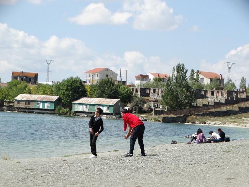 Школьники после уроков отдыхают на берегу озера.