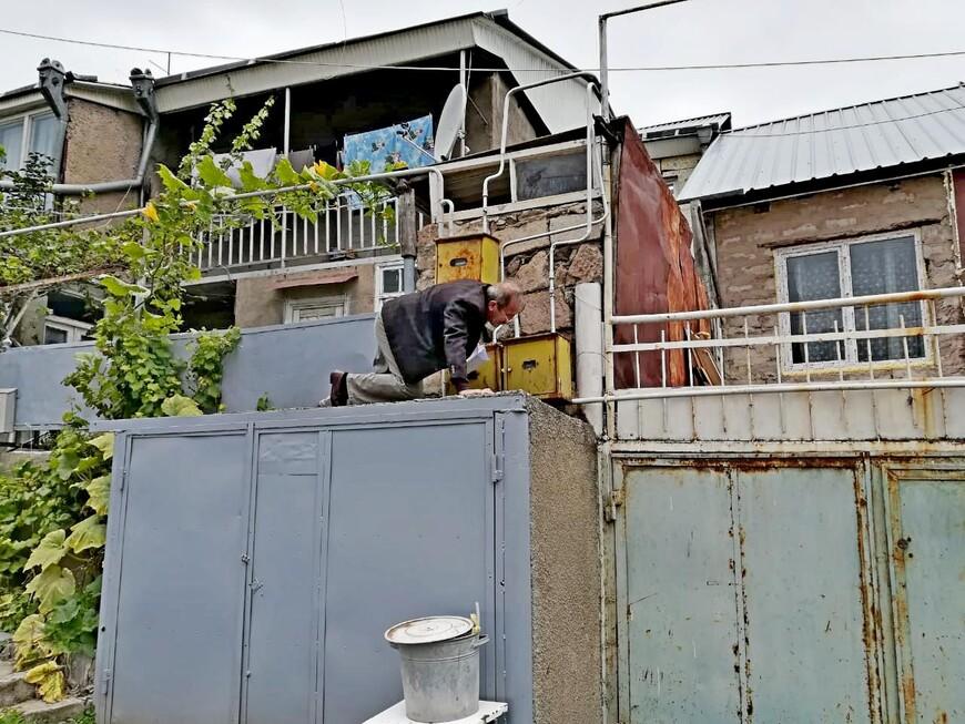 Трубы газопровода в Армении расположены на улице, перед домами, здесь же установлены газовые счётчики. Всё по- честному. В обязанность этого человека  входит снятие показаний, которые он записывает в журнал. Работа трудная и нудная. Домов много, счётчики расположены на разных уровнях, иногда очень высоко.