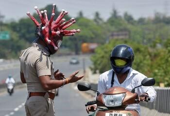 В Индии полицейский в костюме коронавируса отправляет жителей на карантин