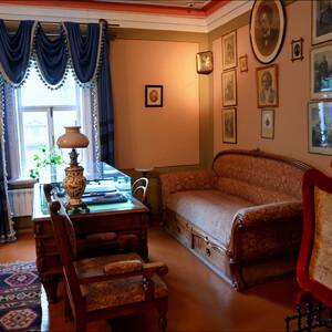 Гостиная мебель - диван, два кресла и шесть стульев, обтянутых шёлком. На столе под зеленым сукном - лампа и два альбома.