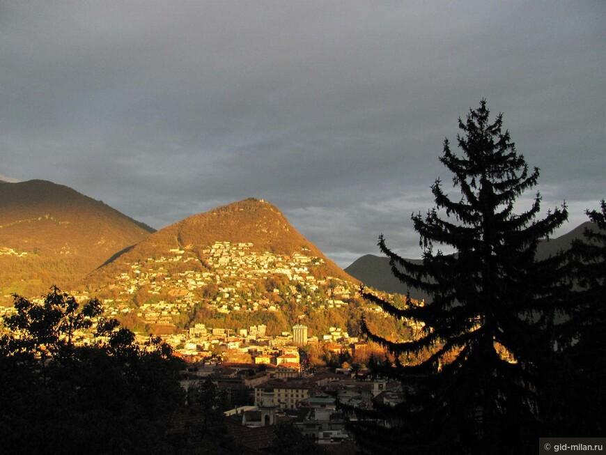Это зимняя фотография. Так последний луч заходящего солнца золотит гору Монте Бре. Кстати, на неё можно подняться на фуникулёре.