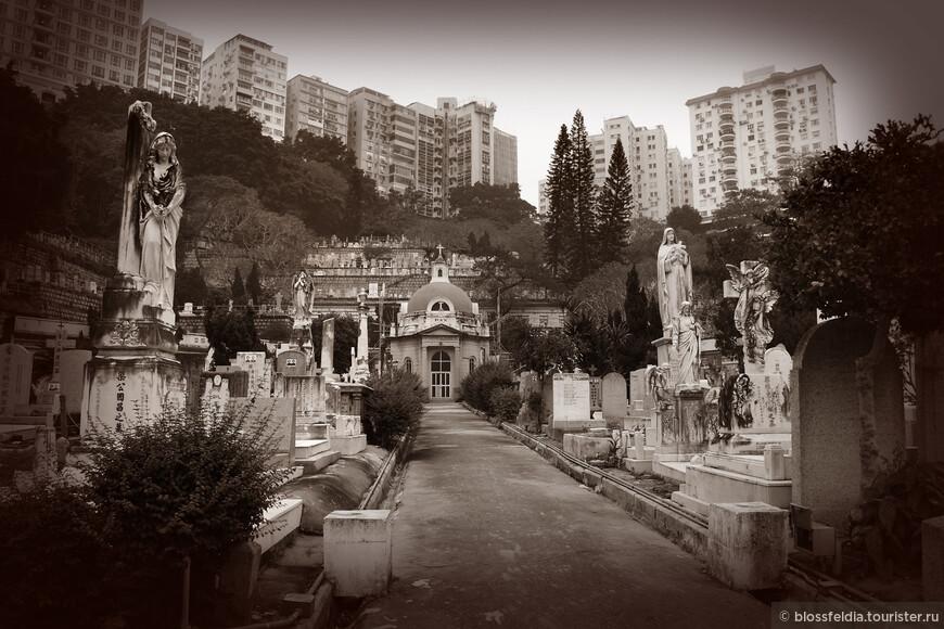 В пасмурную погоду приятно планировать посещение старинных кладбищ, которые должны выглядеть при дожде особенно мрачно.  На остров Гонконг проще всего добраться на пароме Стар Ферри. И вот наконец небоскребы нависают над головой, двухэтажных автобусов становится больше,  появляются двухэтажные трамваи. Пока магазины закрыты (они начинают открываться после полудня), можно покататься по острову куда глаза глядят, тем более с Октопусом это легко. Причем, садясь на трамвай, как и на автобус (да и на такси тоже), надо учитывать левостороннее движение, чтобы найти нужную остановку и уехать в нужном направлении. На втором этаже трамвая открываются окна, а из окон открывается потрясающий вид на улочки Гонконга, на магазинчики, среди которых мелькали 7-eleven, на огромные рекламные щиты.  Чтобы ориентироваться в городе, я приобрела в книжном магазине самый толстый, самый подробный атлас дорог для автовладельцев, естественно на китайском, хотя основные названия имели перевод на английский.