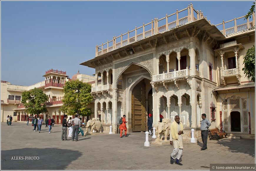 Выходим через роскошные главные ворота на оживленные улицы города и идем вдоль высокой стены.