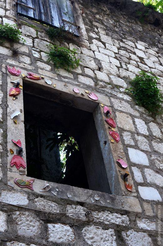 Этот дом располагается на коротенькой улочке, ведущей к дворику с деревом. Дом заброшен - это удивительно - в Которе все дома, в принципе, жилые. Этот - без крыши, внутри буйная растительность. А пустые провалы окон украшены странными аппликациями.