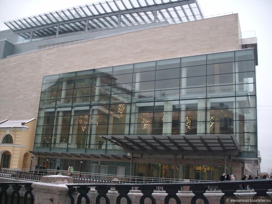 Старая Мариинка  отражается в стекле нового сооружения. Их разделяет канал, но соединяет странный висячий коридор, протянутый через канал.