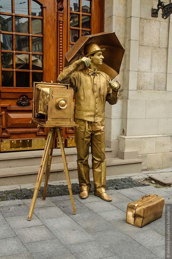 Эпатажный уличный фотограф-статуя. Только фотографирует не он, а фотографируются с ним. За пожертвование в золотой чемоданчик.