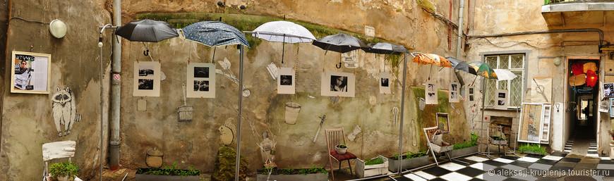 Внутренний дворик с зонтиками и экспозицией старых фото.
