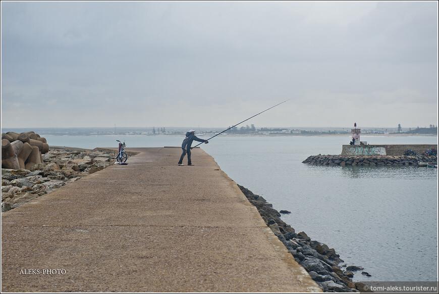 Рыбак на пирсе. А справа - небольшой маяк при входе в искусственно созданную бухту...
