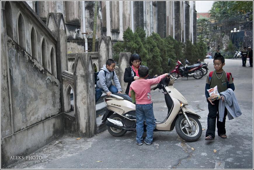 Семейство усаживается на мотоцикл после службы. В храме было довольно много детей...