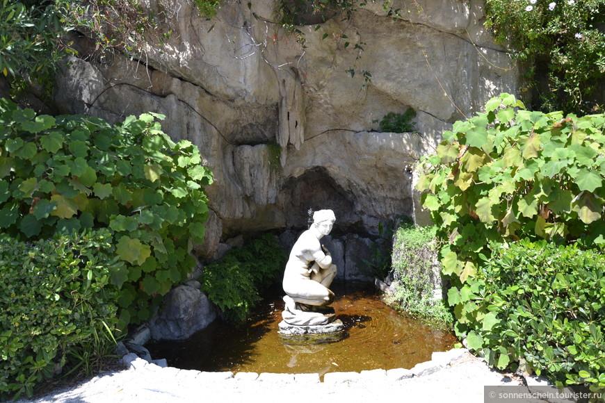 На противоположной от входа в здание стороне сада – изумительная по дизайну композиция. Целая стена растений и вкрапленных между ними древних скульптурных фрагментов. Заканчивается коллаж настоящим гротом с фонтаном. В центре чаши с водой находится мраморное изваяние сидящей нимфы. Грот утопает в зелени адиантумов, куфей, монстер и циперусов.