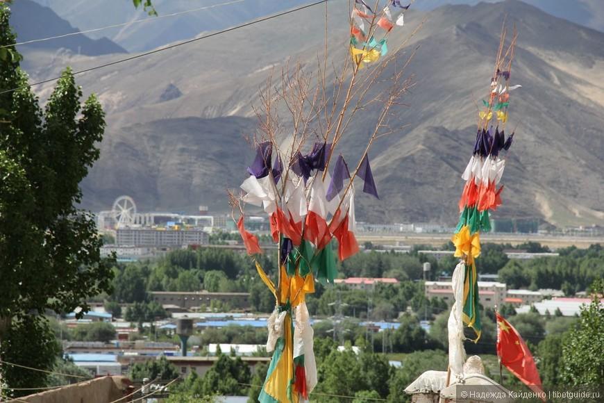 Бонские и китайский флаги в тибетском буддистском монастыре. Вид на Лхасу.