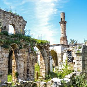 По этому сооружению можно изучать историю средиземноморского побережья страны. На месте языческого храма, снесенного во времена Византийской империи, христиане построили церковь Девы Марии, в которой хранили икону, написанную Святым Лукой. Турки-сельджуки, завоевавшие побережье моря, превратили церковь в мечеть, пристроив к ней минарет. С 1361 года сюда возвращается католическая, а с 1373 года и до XV века - православная церковь. При Шехзаде Коркуте она снова становится мечетью, возможно, ею бы она и осталась. Но пожар 1896 года превратил строение в развалины. При этом верхушку минарета срезало, будто мечом.