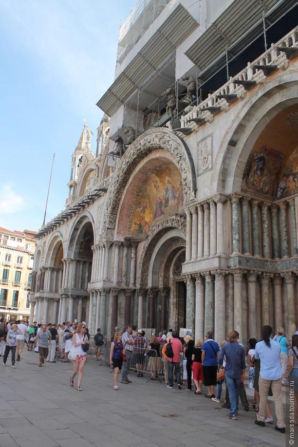 Мраморный главный фасад восходит к 13 веку. Он богато украшен мозаиками и барельефами
