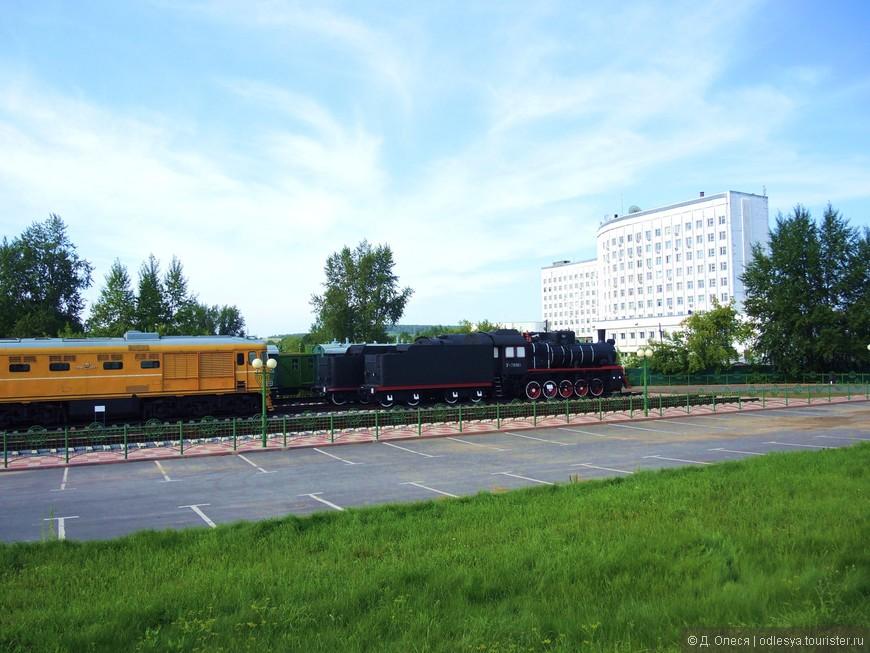 музей железнодорожной техники а за ним здание Кемеровского отделения РЖД