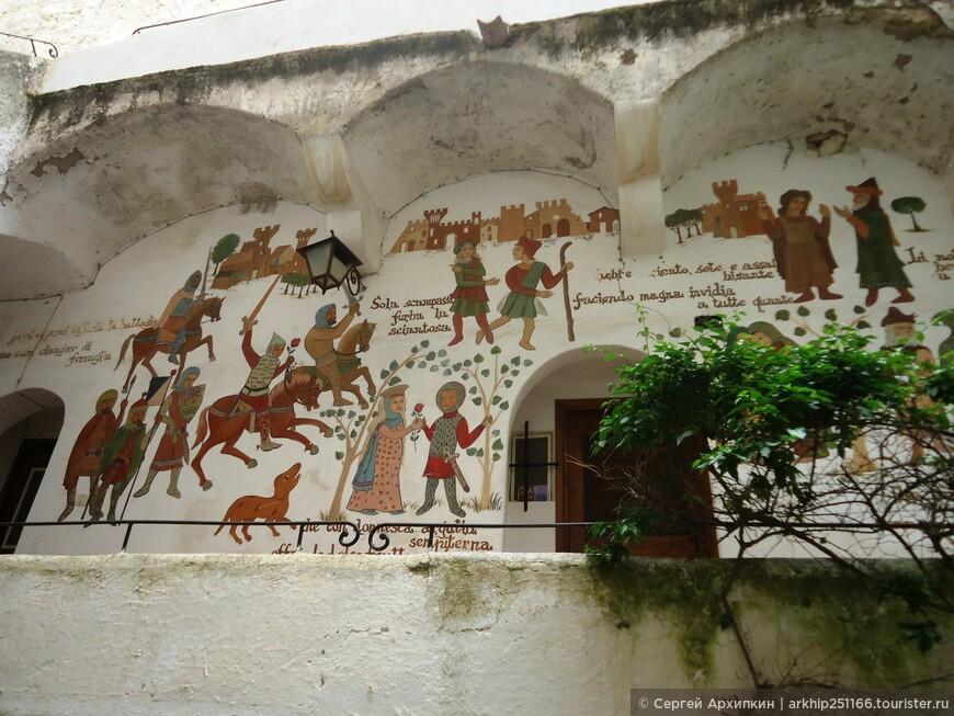 Часть белых стен разрисована на средневековые темы