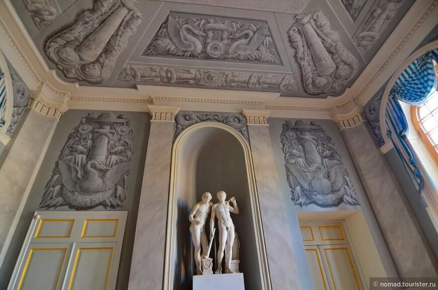 Интерьеры Большого Дворца.  Вестибюль — это уже и первый парадный зал дворца. Торжественность придают ему графически четкая одноцветная роспись в технике гризайль, общий серебристо-серый в сочетании с белым холодноватый колорит, крупных форм скульптура.