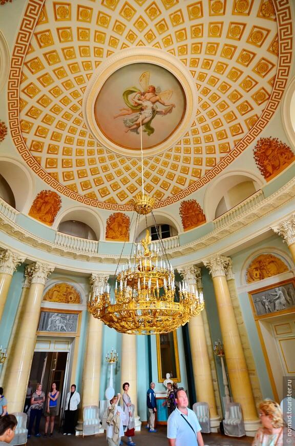 Интерьеры Большого Дворца. Овальный зал.  Двусветный, высотой в два этажа, соединяющий две анфилады, Овальный зал — самый сложный по архитектурному решению, самый большой и великолепный во дворце. Он расположен в центре здания по главной оси всего ансамбля. Это поистине архитектурный и композиционный центр дворца.