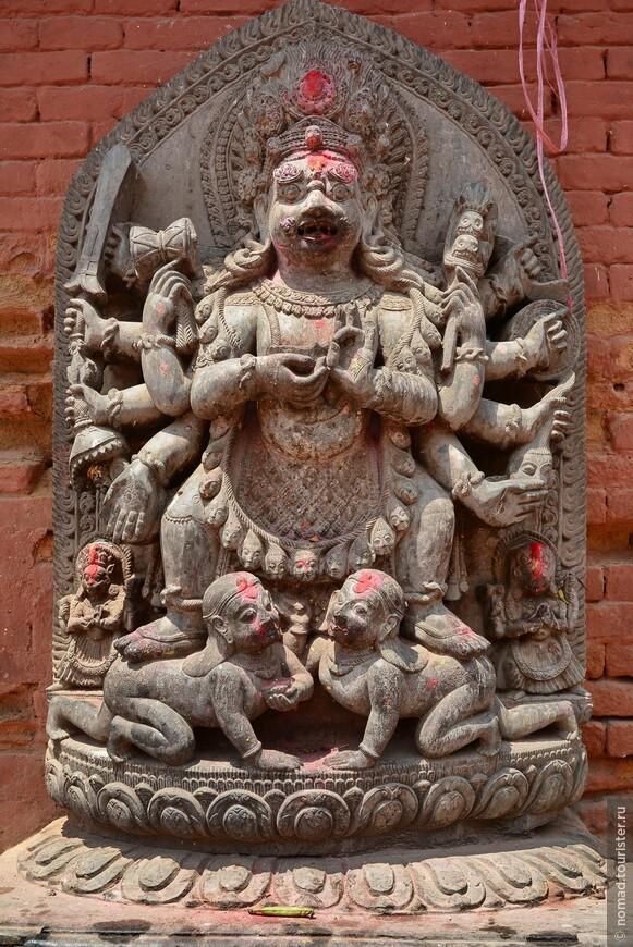 Площадь Дурбар. Статуя бога Бхайраба. Это божество имеет множество различных форм. В частности является тантрической формой Шивы. Его изображают обнаженным, черного или темного цвета. Иногда на картинах он бывает белым. У него множество рук, но обычно одна голова. В руках -- оружие, черепа, лассо, палка с тремя черепами. Он носит ожерелье на шее, венок и корону из черепов. У Бхайраба непокорные волосы. Может носить сандалии и часто стоит на лежащей фигуре.
