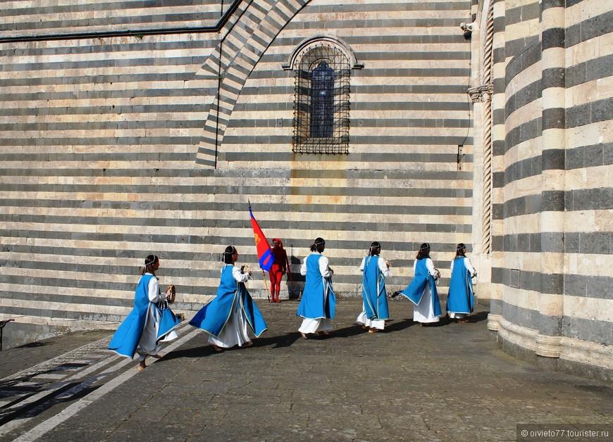Все персонажи парада направляются в собор. С бокового входа.