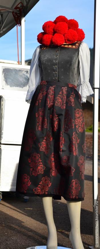 """Неотъемлемой частью женского наряда, в котором преобладает черный и красные цвета, является """"болленхут"""" — шляпка с """"вишнями"""". Соломенная шляпа, украшенная несколькими шерстяными помпонами — родом из городка Гутах в центре Шварцвальда. Популярной она стала в середине XVIII века. Замужние женщины украшают ее черными помпонами, а девушки — красными."""