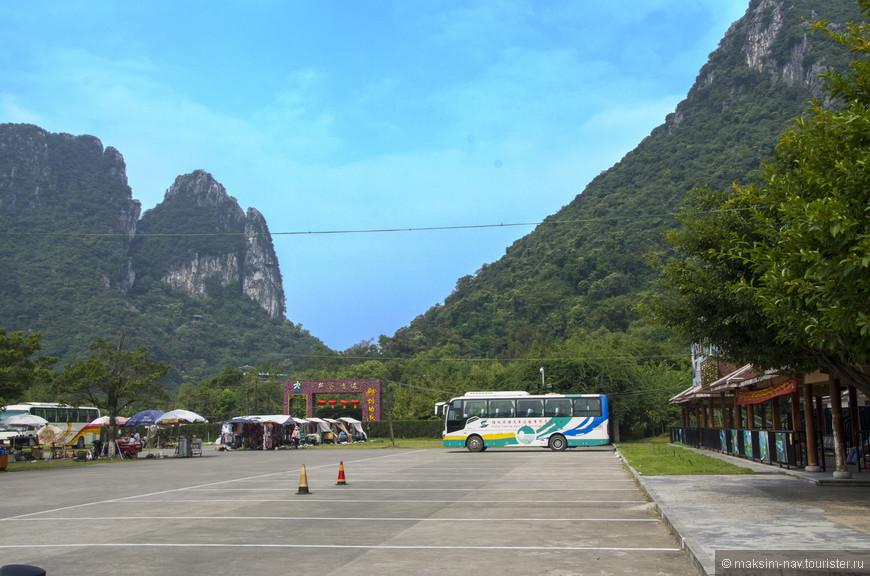 Пещера Тростниковой флейты находится в одноимённом парке в семи километрах к северо-западу от центра города, у основания горы Гуанминшань. Паркинг у входа в парк.