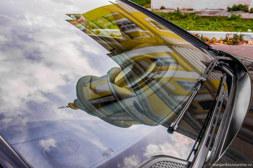 отражение колокольни в машинах на ближайшей парковке