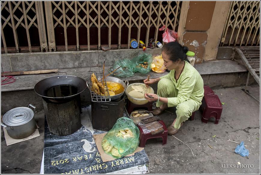 """Прямо на улице хозяйки готовят еду для себя и для своих соседей. Вьетнамцы, как и многие другие южные народы, очень любят готовить пищу на свежем воздухе. Потом ее аппетитно едят, усевшись на низенькие скамеечки, которые я прозвал """"пигмейскими""""."""