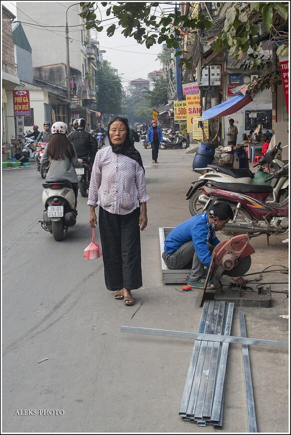 Чего только мы не увидели на этой улице — одной из, наверно, тысяч маленьких улочек большого Ханоя. Вот, например, специалист по металлическим конструкциям — работает прямо на улице. Тротуаров на таких улицах у них нет. Здесь же ездят — здесь же работают прямо на проезжей части.