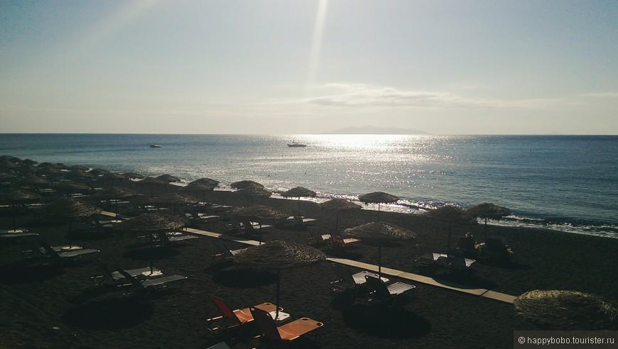 пляж в Камари с черным вулканическим песком