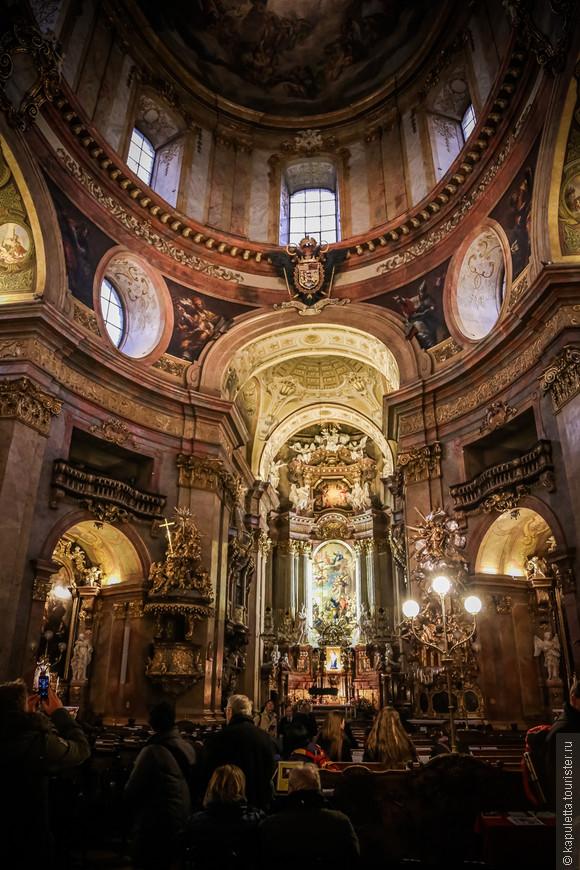 """М. Роттмайр, расписал  купол своими фресками; М. Альтомонте  """"взорвал"""" тот век  своими пластинами для алтаря. Почти все крупные мастера того времени занимались ее украшением. Под алтарем Святого семейства хранятся реликвии Св. Донатуса."""