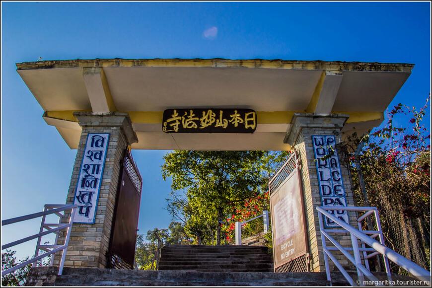 вид на ворота со стороны ступеней, на которы по-тибетски и на ангдийском написано: Пагода Мира