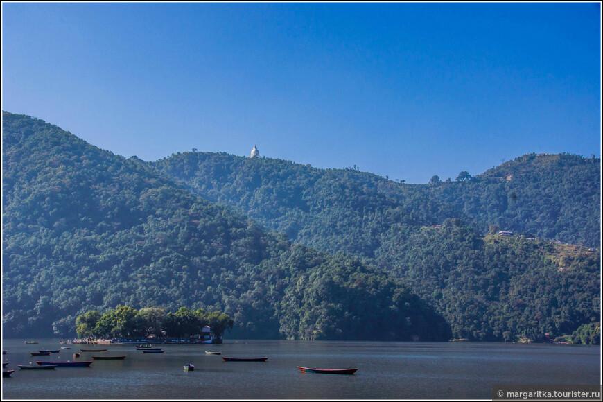 """вид на Ступу """"Мир во всем мире"""" с набережной Покхары. Один из путей к Ступе может лежать на лодке чорез озеро Фева (Пхева), а там круто в гору по пешеходным тропам, коих, по словам местных, там существует множество.  Второй способ - автобусом до развилки и там пешком по дороге вверх до начала по степеней. А третий доехать до самих ступеней на такси или арендованной машине. Такси стоит сущие копейки. В моем отеле такси мне прилагалось, как гостиничного сервиса."""