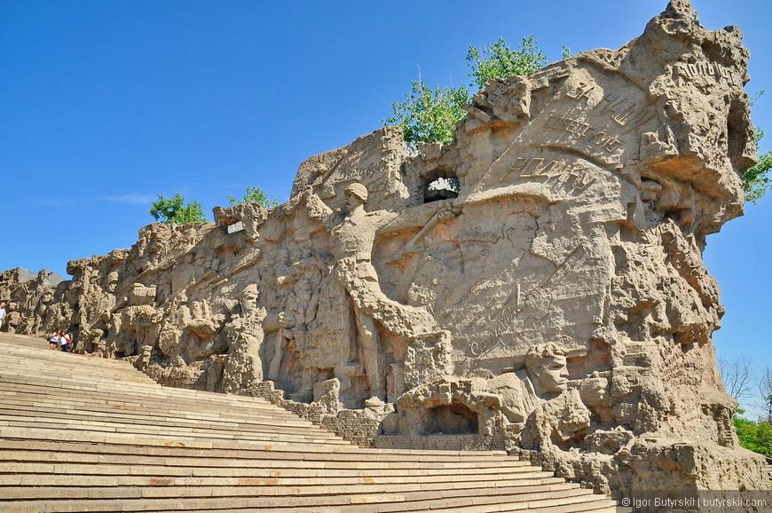 """05. Поднимаясь по гранитной лестнице к Площади героев, можно рассмотреть """"Стены-руины"""", уменьшающиеся и сходящиеся в далекой перспективе. Длина стен - 46 м, высота - 17,5 м, ширина лестницы у начала стен - 40 м, к концу сужается до 18 м. Ширина (толщина) самих стен - 4,5 м. С тыльной стороны их проходят 2-метровой ширины гранитные лестницы, газоны с деревьями."""