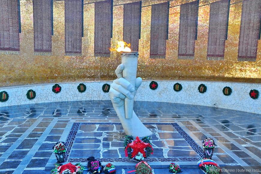 22. Вдоль стены Зала - двухметровая, постепенно поднимающаяся дорожка-пандус. Стены Зала облицованы мозаикой из золотистого стекла. На стене, по кругу, расположены 34 мозаичных траурных Знамени, выполненных из красной смальты и символизирующих всех погибших в Сталинградской битве. На Знаменах увековечены имена погибших защитников города (всего 7200 человек).